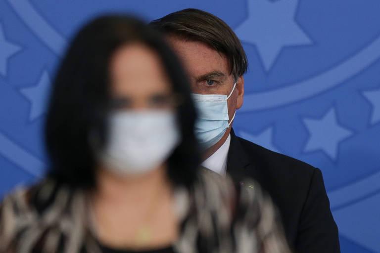 O presidente Jair Bolsonaro, ao fundo, observa a ministra Damares Alves (Mulher, Família e Direitos Humanos) em cerimônia no Palácio do Planalto