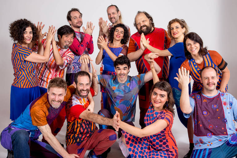 Treze integrantes do grupo posam para foto batendo suas mãos