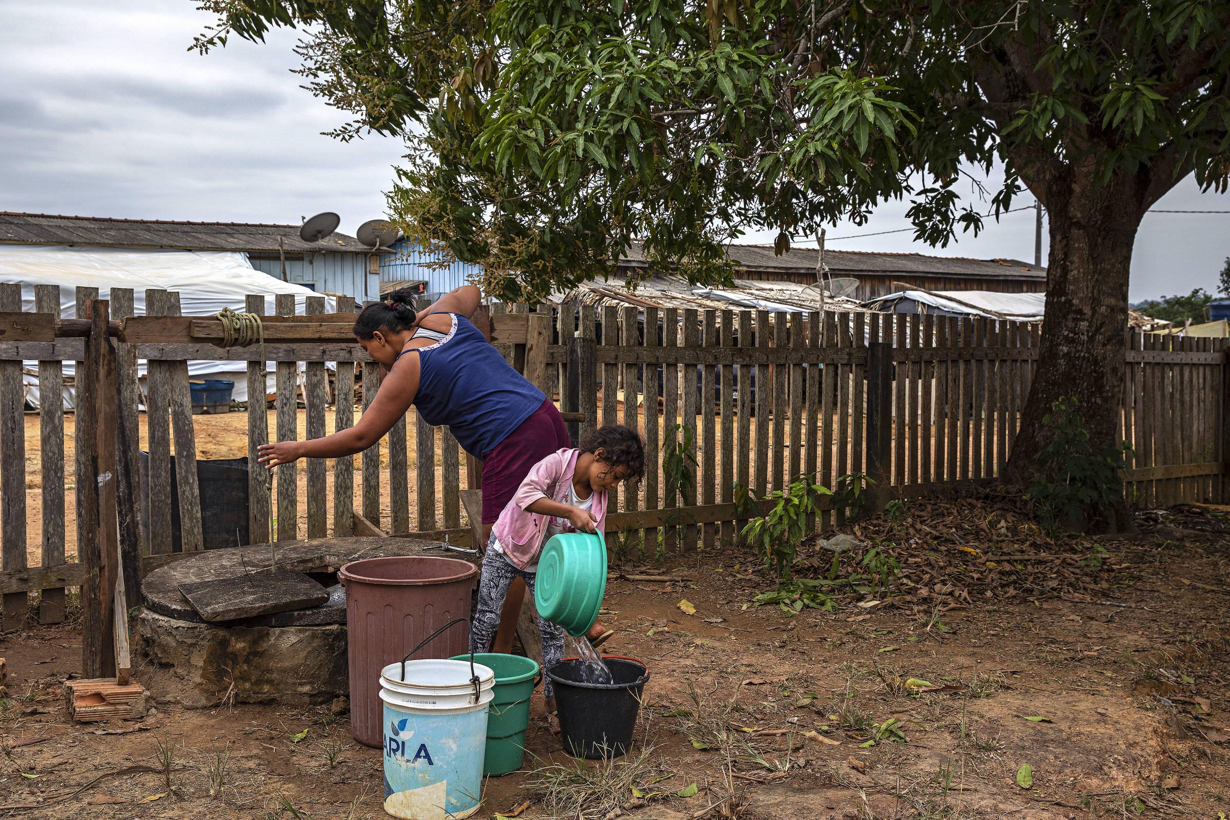 Sem-terra pega água de um poço em uma casa vizinha ao acampamento na vila do Rio Pardo