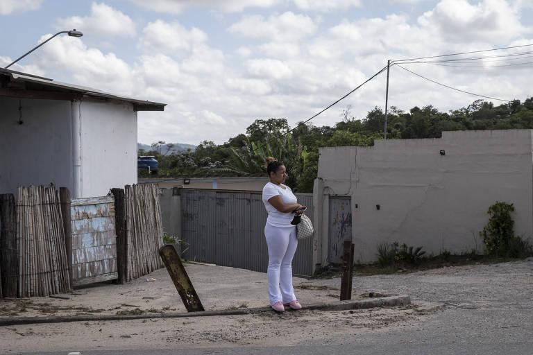 Uma mulher de branco esperando ônibus numa esquina