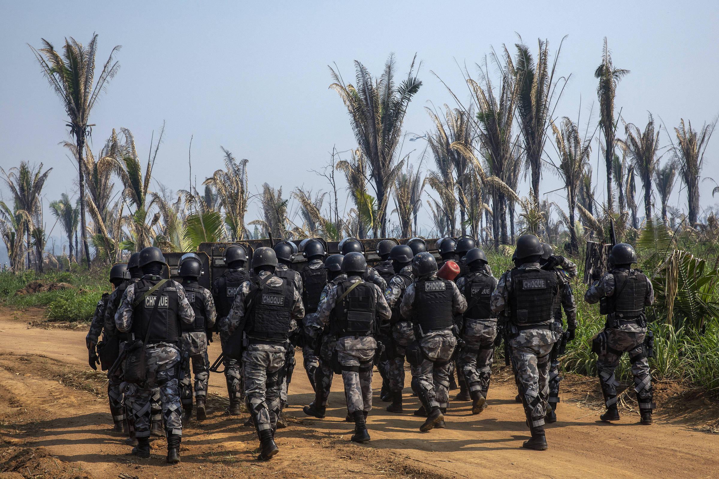 Tropa de choque da PM caminha dentro da Floresta Nacional Bom Futuro, em Rondônia, para cumprir mandado de reintegração de posse de invasão dentro da reserva, em 2019