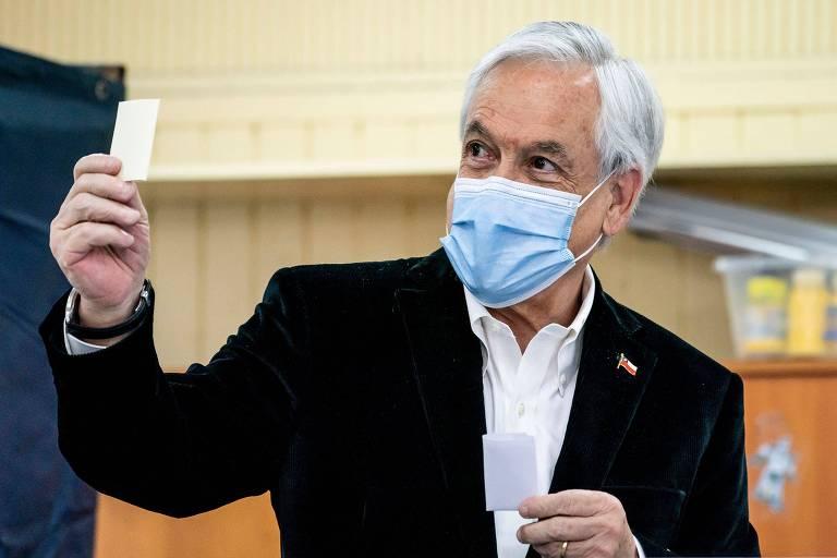 O presidente chileno Sebastián Piñera posa com cédula durante o referendo. Ele veste uma máscara de proteção.