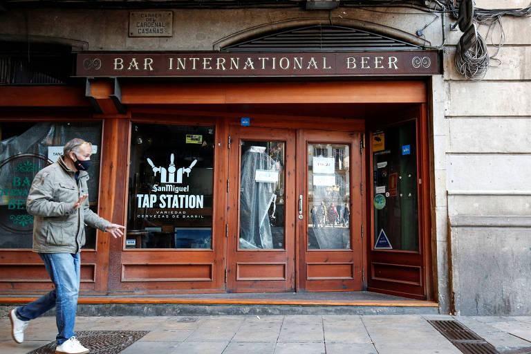 Homem com máscara passa em frente a bar em Barcelona; estebelecimentos deverão cumprir toque de recolher