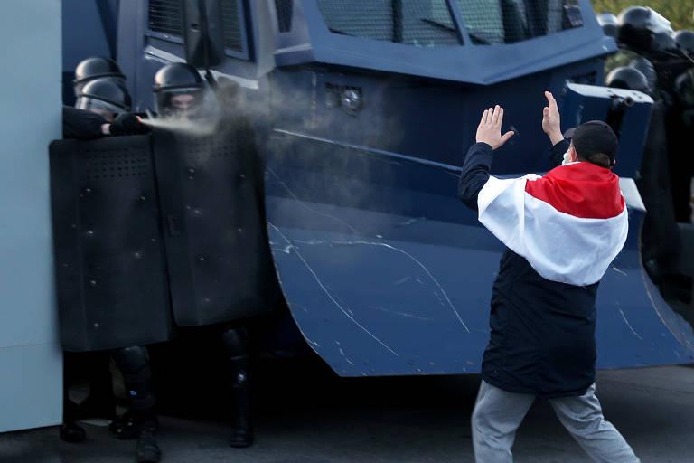 Policiais de capacete e escudo jogam gás em manifestante com bandeira branca, vermelha e branca
