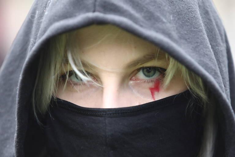 Moça loira de máscara preta e raio vermelho sob o olho
