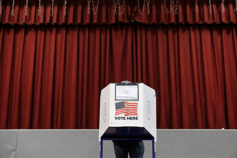 A person fills out a ballot in a privacy booth at a polling station located in the Monsignor John D. Burke Memorial Gym at the Church of the Holy Child in Staten Island, during early voting in New York City, U.S., October 25, 2020. REUTERS/Andrew Kelly ORG XMIT: PPP- AJK008