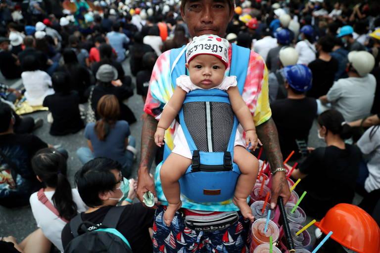 No meio de uma multidão, um homem carrega um bebê em um suporte em sua barriga, durante um protesto em Bangcoc, na Tailândia