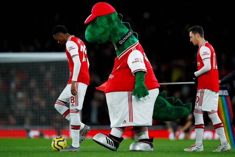 Özil (à dir.) e Willock deixam o campo ao lado da mascote do Arsenal