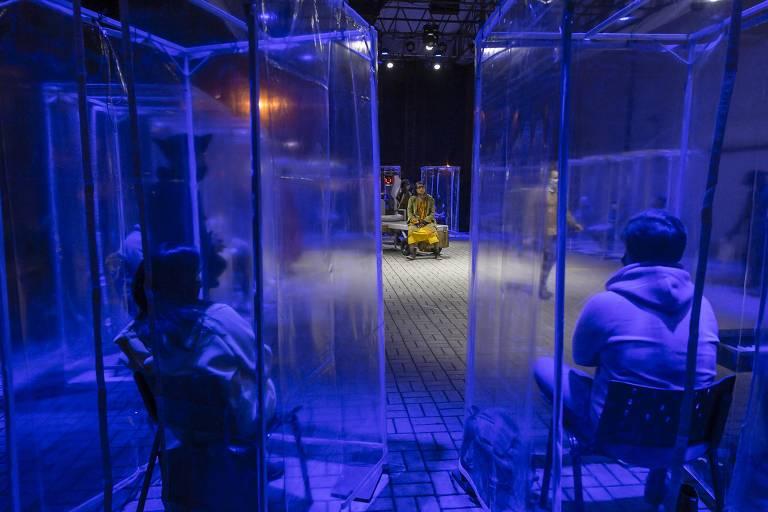 Plateia assiste a peça em cabines transparentes para se proteger do coronavírus