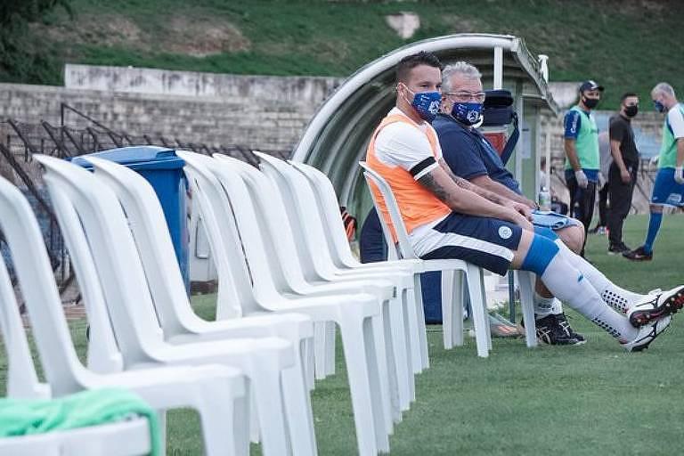 Imagem mostra uma fileira de cadeiras de plástico ao lado do campo e, na última delas, está sentado o goleiro do São Bento