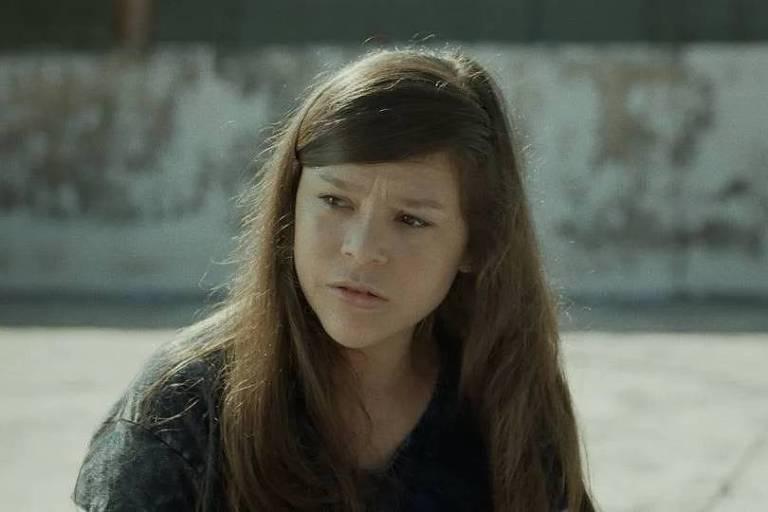 Imagem mostra o rosto da personagem Valentina; ela tem cabelos longos e lisos, castanhos, e está séria