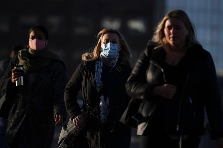 Pedestres caminham pela Ponte de Londres pela manhã em direção ao centro de Londres, com máscaras.
