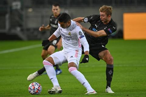 Real Madrid's Brazilian midfielder Casemiro (L) and Moenchengladbach's German midfielder Christoph Kramer vie for the ball during the UEFA Champions League group B football match  Borussia Moenchengladbach v Real Madrid in Moenchengladbach, western Germany on October 27, 2020. (Photo by Ina Fassbender / AFP)