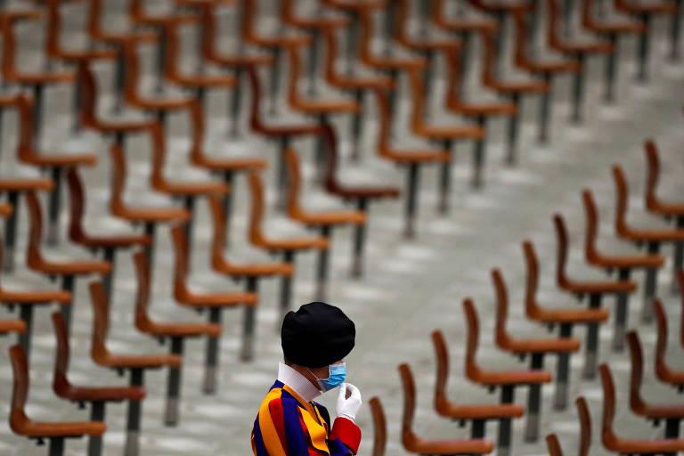 À frente de dezenas de cadeiras vazias, um guarda suíço vestido com um chapéu estilo bearskin ajusta sua máscara facial antes da audiência geral semanal realizada pelo Papa Francisco no Vaticano