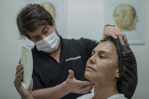 SÃO PAULO, SP, BRASIL, 27-10-2020: A harmonizaçao facial virou uma febre entre os procedimentos estéticos. Durante a pandemia, a procura sobre esse conjunto de técnicas chegou a crescer mais de 500% em mecanismos de busca na internet. Na foto o dermatologista  Ivan Rollemberg (33), durante procedimento de harmonização Facial na relações públicas Daniela Raddi (45). (Foto: Bruno Santos/ Folhapress) *** AGORA - SHOW ***