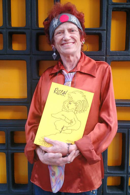 mulher de certa idade com cabelos curtos e vermelhos segura um livro nos braços e posa para foto