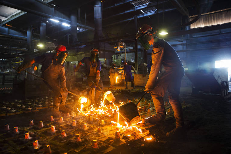 Operários entornam ferro derretido em altíssima temperatura