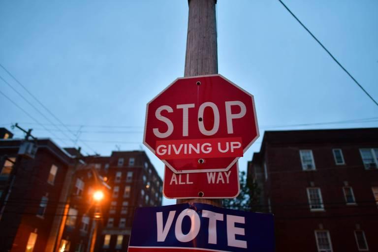 Intervenção em poste na Filadélfia incentiva eleitores a votar construindo a frase 'Pare de desistir e vote' a partir de uma placa de 'pare', adesivos e um cartaz escrito 'vote'