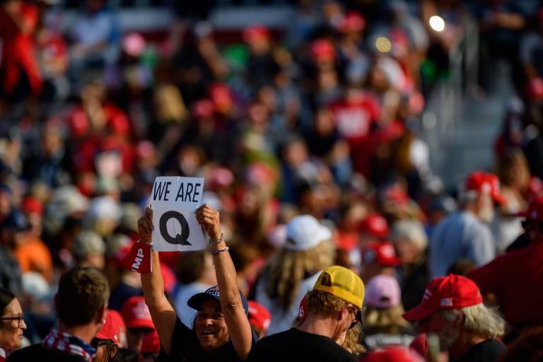 Mulher segura cartaz com a frase 'nós somos Q', em referência ao grupo cospiracionista QAnon, em evento de Donald Trump na Pensilvânia