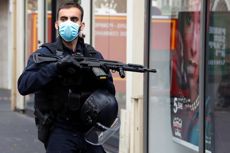 Policial de máscara segura fuzil