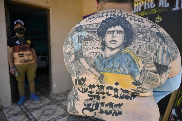 """O pizzaiolo Guillermo Rodríguez mostra suas tatuagens dedicadas a Diego Maradona. Nas costas, exibe o ídolo com a camisa do Boca Juniors e da seleção argentina, além da mensagem em letras grandes """"Obrigado, Deus"""""""