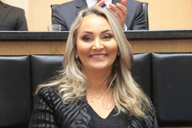 Mulher loira de cabelo comprido e blusa preta sorri