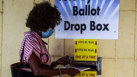 A woman drops her ballot by mail at Broward County Supervisor Of Elections Office in Lauderhill, Florida on October 5, 2020. (Photo by CHANDAN KHANNA / AFP)