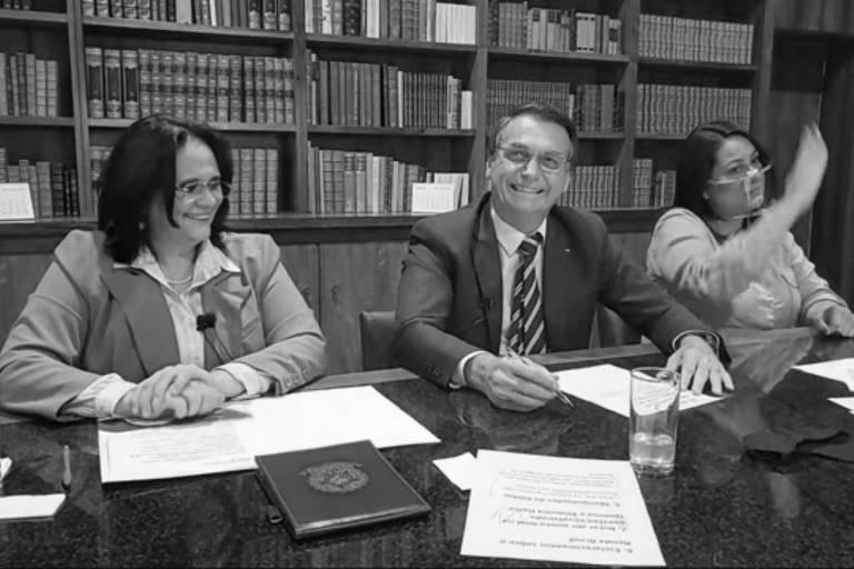 Em frente a uma estante de livros, a ministra Damares Alves, à esquerda, o presidente Jair Bolsonaro, no centro e a tradutora de Libras se sentam a uma mesa. A ministra e o presidente riem.