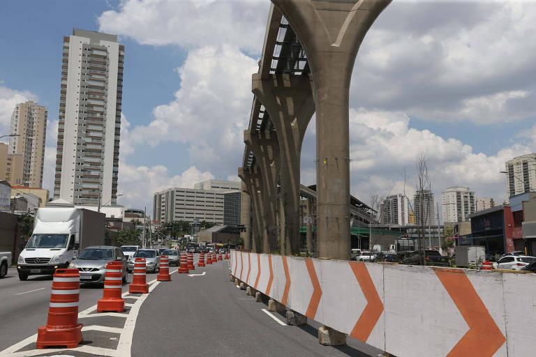 Via urbana com carros, cones, obra do metrô e edifícios ao fundo
