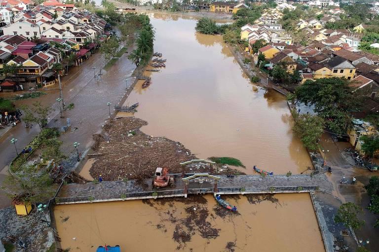 Vista aérea mostra ponte sobre rio inundado, com casas às margens