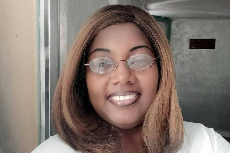 moça negra de blusa branca, óculos e cabelos lisos castanhos claros sorri para a câmera