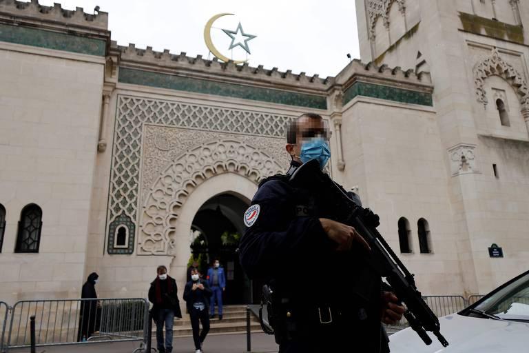 Policial armado em frente a mesquita, onde várias pessoas entram