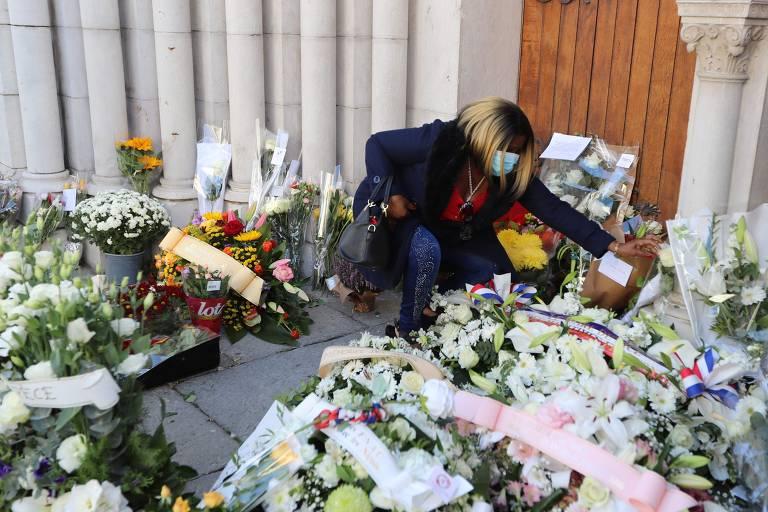 Entrada de igreja com várias flores, mulher coloca flores também