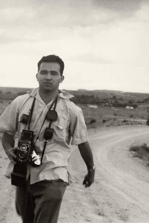 Fotografia mostra o fotógrafo Luciano Carneiro, um homem com cerca de 35 anos, andando com suas câmeras penduradas junto ao corpo, durante a produção de uma reportagem