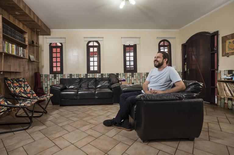 Homem sentado em sofá, em sala com piso frio e painel de madeira na parede