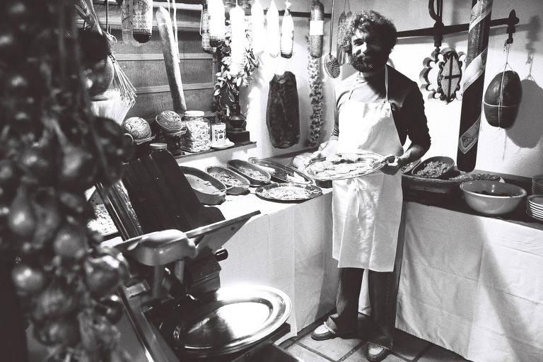 Foto preto e branco com Walter Mancini segurando pratos de seu restaurante