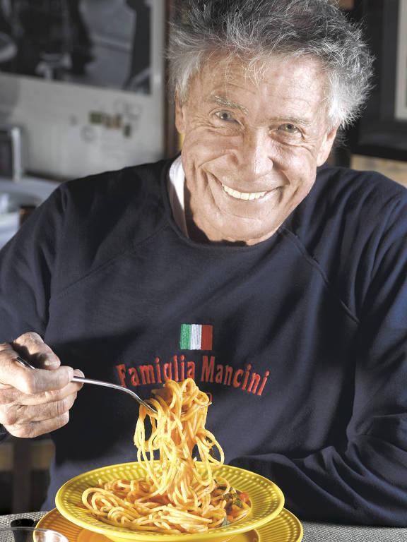 Walter Mancini sorri em frente a uma macarronada
