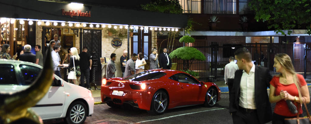 Fachada do restaurante Famiglia Mancini, com carros importados