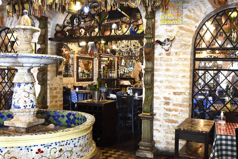 Ambiente do restaurante Famiglia Mancini, com mesas e chafariz