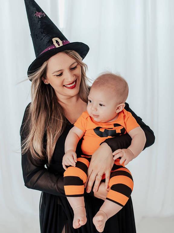 Mãe sorridente, vestida de bruxa, segura bebê