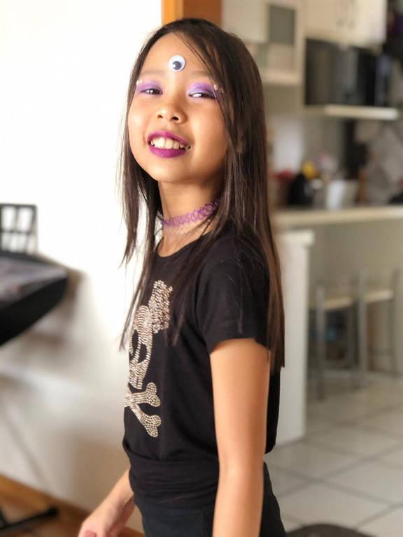 Menina de cabelos pretos, fantasiada e maquiada para o Halloween, sorri para a câmera