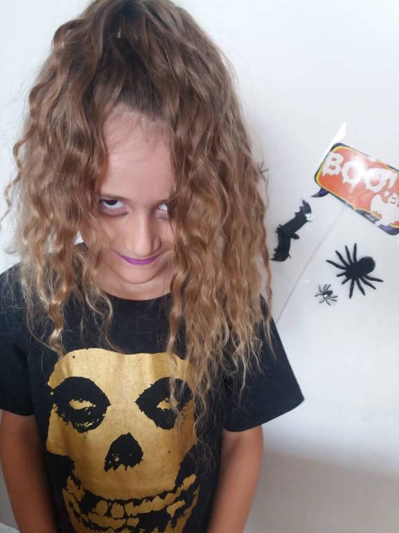 Menina de cabelos loiros, fantasiada e maquiada para o Halloween, sorri sinistramente para a câmera