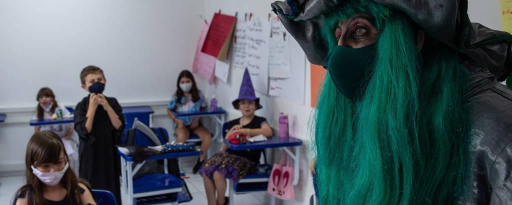 Uma bruxa de cabelos verdes e várias crianças fantasiadas em uma sala de aula