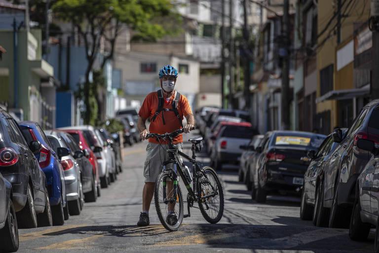 Um homem de bicicleta e máscara no meio da rua