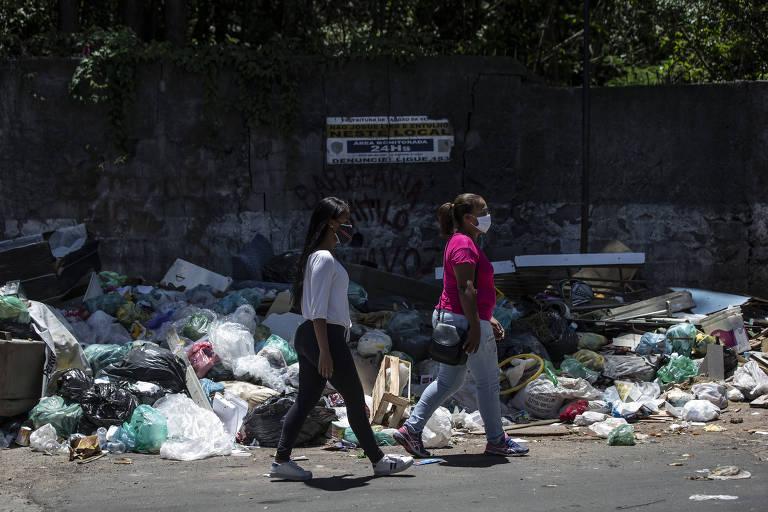 Duas mulheres caminhando numa rua cheia de lixo