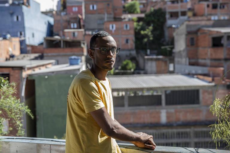 Adilson, um rapaz negro, magro e de óculos, no fundo da casa, de onde é possível avistar várias construções inacabadas no bairro da periferia