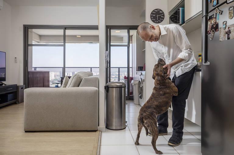 Homem de branco brinca com cachorro em apartamento