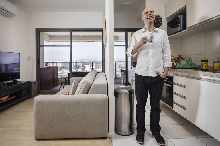 Homem de branco, em pé, com xícara na mão
