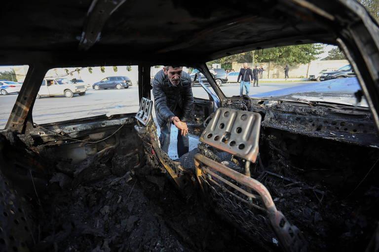 Em Barda, no Azerbaijão, homem observa interior de carro atingido devido a conflito pela região de Nagorno-Karabakh