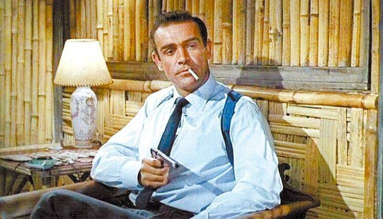 Homem segura arma enquanto fuma